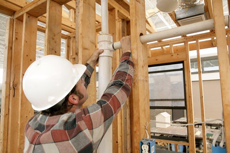 Tubulação de conexão do trabalhador da construção fotos de stock