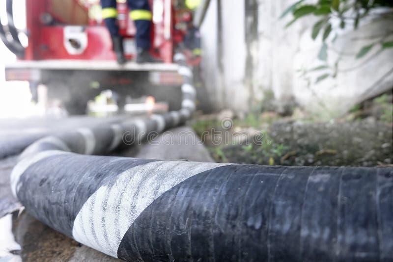 Tubulação de mangueira ao firetruck imagens de stock