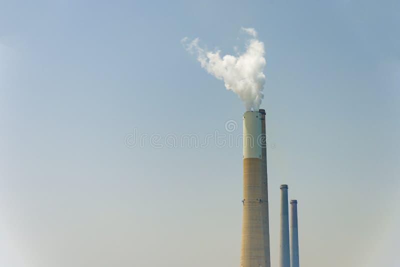 A tubulação de que o fumo vai contra o céu cinzento O conceito da polui??o do ar imagem de stock