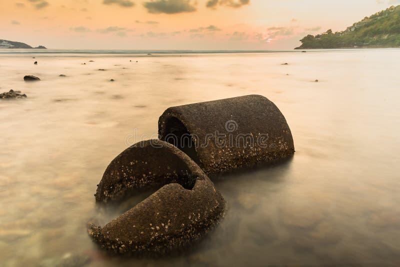 A tubulação do cimento das ruínas no mar no tempo do por do sol Seascape bonito tail?ndia imagem de stock
