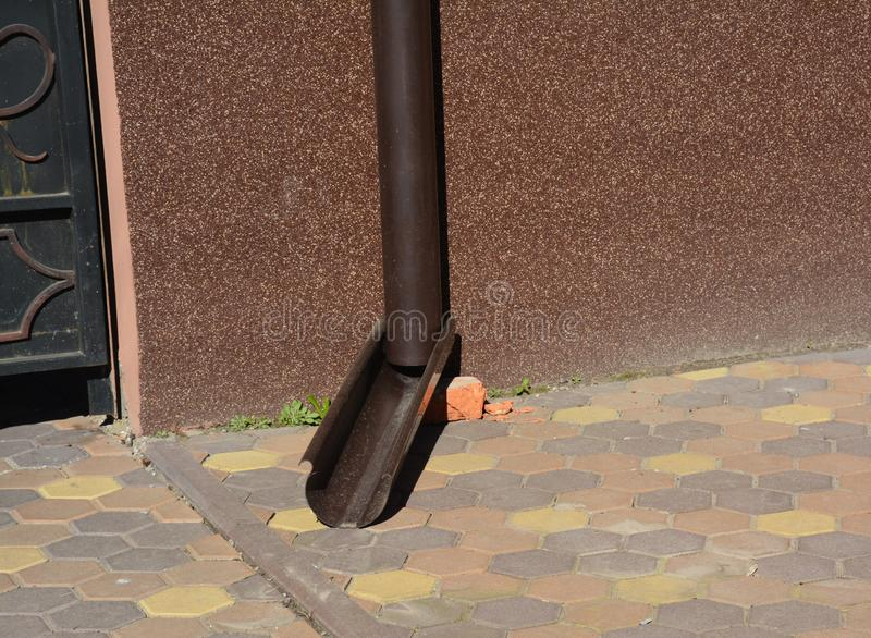 Tubulação do downspout da calha do telhado perto da parede da fundação da casa fotos de stock