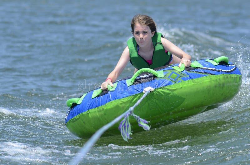 Tubulação do jovem adolescente atrás de um barco imagem de stock royalty free
