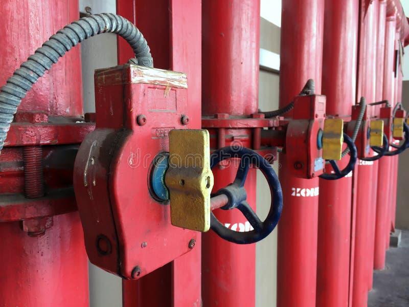Tubulação e interruptor vermelhos do fogo do ferro para formação ajustada da água em uma fileira longa foto de stock