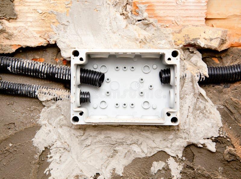 Tubulação elétrica da canalização da bobina na caixa encaixada na parede fotografia de stock