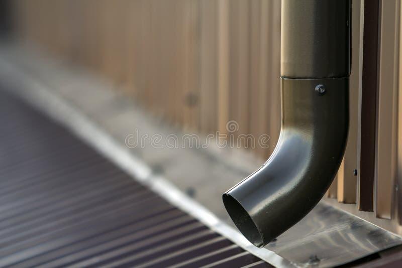 Tubulação nova do sistema do metal da calha de Brown Construção vertical para sair a água de chuva do telhado da construção na pa fotografia de stock