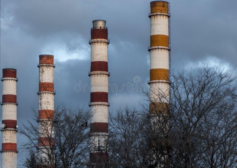 Tubulação quatro industrial alta em um fundo do céu azul com fumo imagens de stock