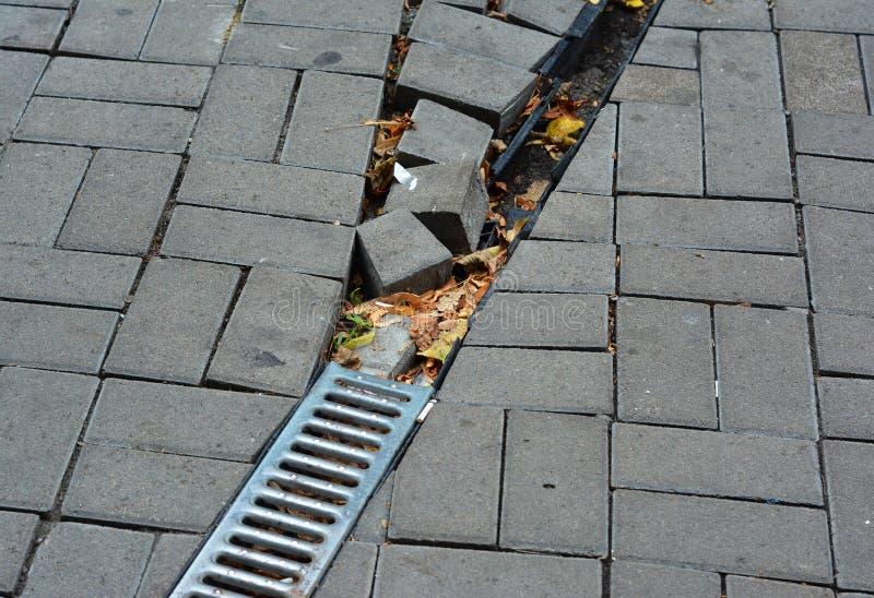 Tubulação quebrada do downspout da calha da chuva para o runoff do telhado com drenagem danificada da água aberta no pavimento ao imagens de stock royalty free