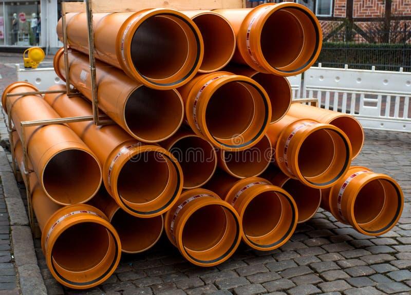 Tubulações alaranjadas do PVC empilhadas no canteiro de obras fotografia de stock royalty free