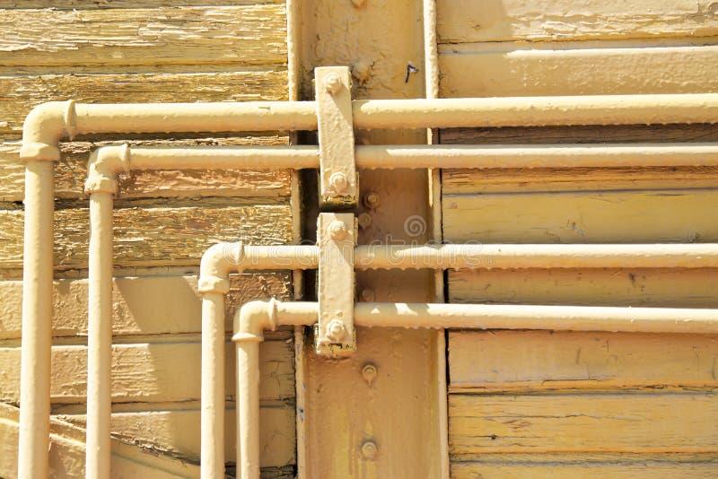 Tubulações amarelas velhas na parede de madeira Fundo urbano do país do Grunge do risco Textura para seu projeto fotografia de stock