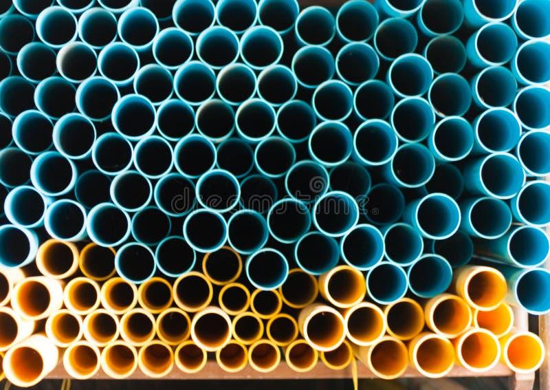 Tubulações de água azuis e amarelas do PVC no armazém fotografia de stock