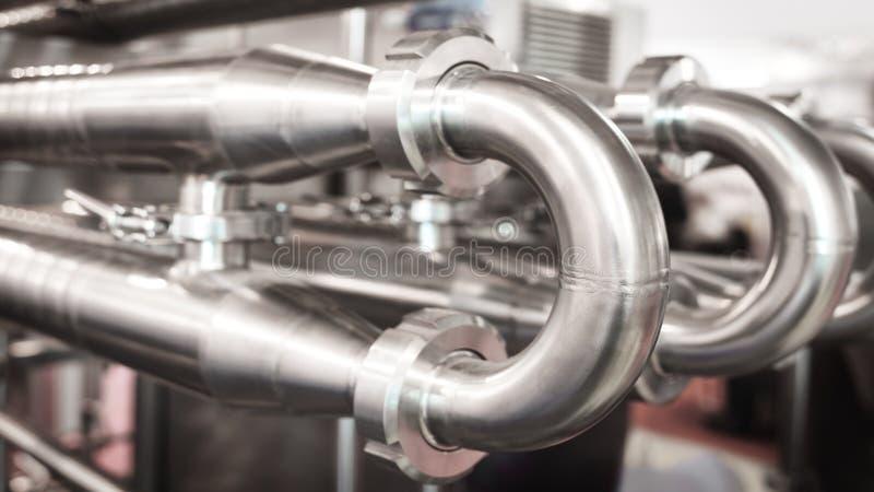 Tubulações de aço inoxidável na fábrica Construção na produção alimentar, fundo abstrato da indústria fotografia de stock