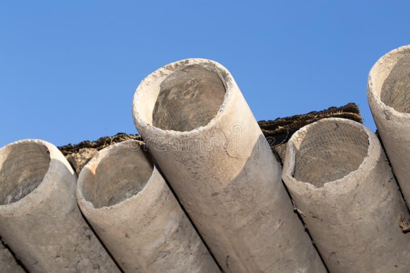 Tubulações do cimento de asbesto contra o céu azul imagens de stock royalty free