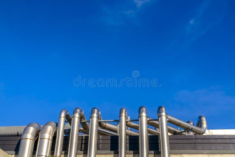 Tubulações do metal de uma construção contra o céu azul vívido imagem de stock