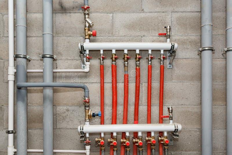 Tubulações do sistema de fonte do aquecimento e da água no fundo de um muro de cimento imagem de stock