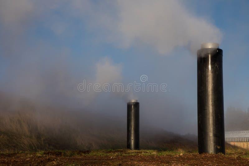 Tubulações geotérmicas na paisagem gramínea com céu azul foto de stock