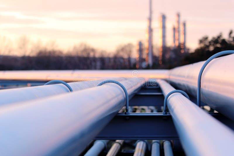 Tubulações longas de aço na fábrica do óleo bruto durante o por do sol foto de stock