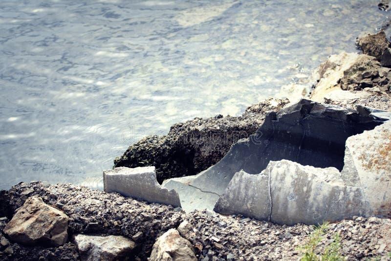 Tubulações velhas com as águas residuais que entram no mar imagens de stock