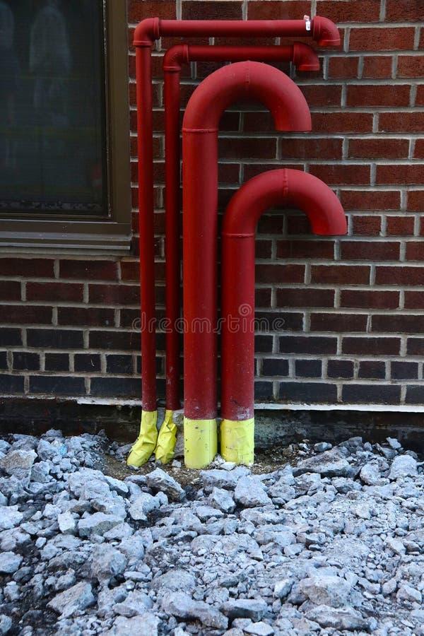 Tubulações vermelhas contra a parede do limiar com pavimento quebrado imagens de stock