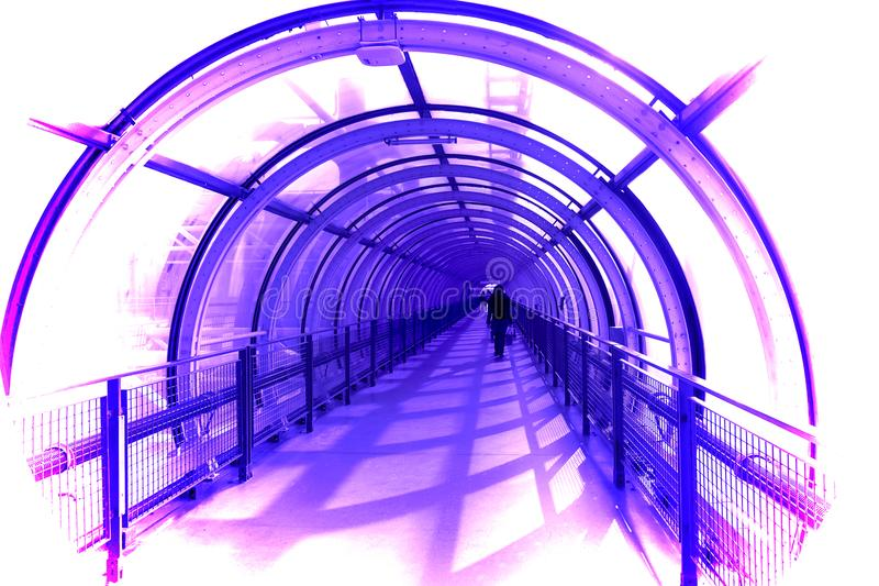 Tubular Pedestrian Walkway. A tubular glass and steel pedestrian walkway located in Lyon, France is represented as a conceptual photograph in vibrant shades of stock photos