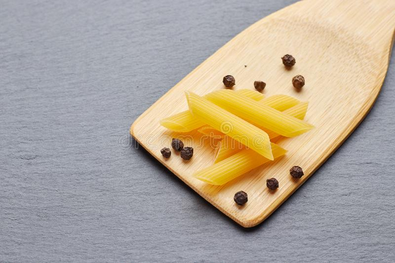 Tubules макаронных изделий с перцем на деревянном шпателе стоковая фотография