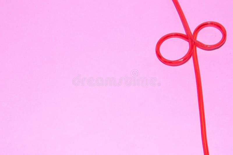 Tubuli per i cocktail su un fondo rosa bevitori immagine stock