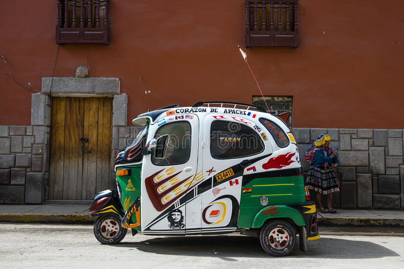 A tuc tuc taxi parked in a street of Pisac. Pisac, Peru - December, 2013: A tuc tuc taxi parked in a street of Pisac royalty free stock photography