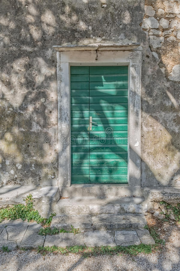 Tucepi village house door. Typical house green door in Tucepi old village in the slope of a mountain Biokovo. Tree shadow texture on the facade royalty free stock photography