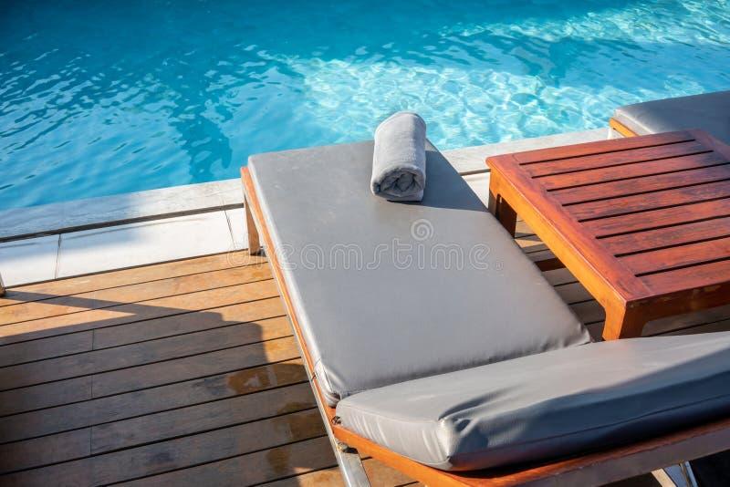 Tuch auf Entspannungspoolbett neben Swimmingpool lizenzfreie stockbilder