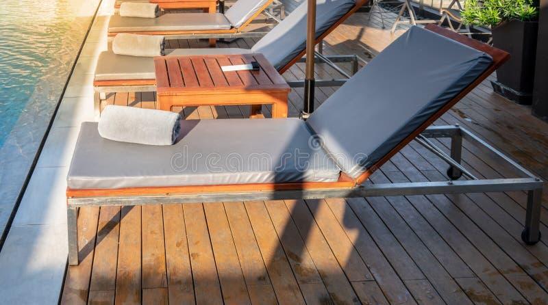 Tuch auf Entspannungspoolbett neben Swimmingpool stockbilder