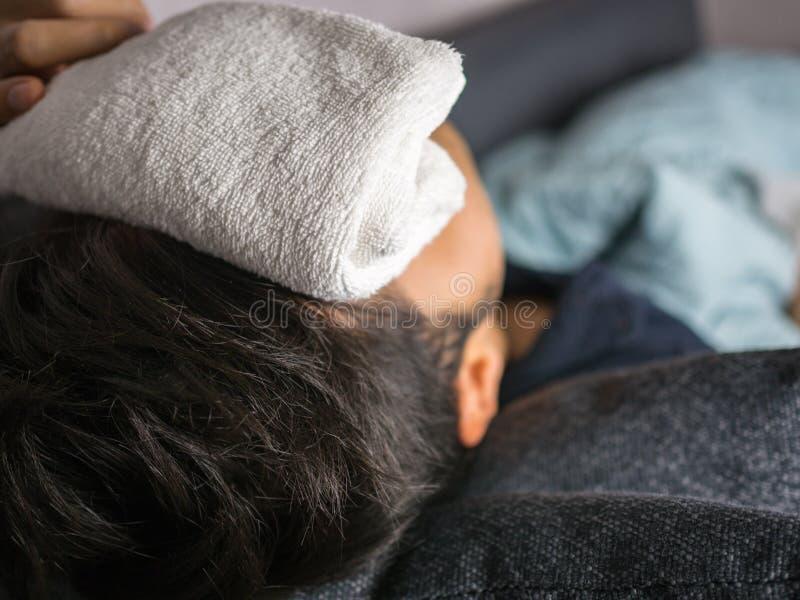Tuch auf Stirn, auf Mann fühlt sich krank lizenzfreie stockbilder