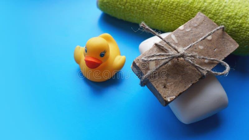 Tuch, Seife und gelbe Spielzeugente auf einem blauen Hintergrund Flaches Lagefoto, Draufsicht lizenzfreie stockfotografie