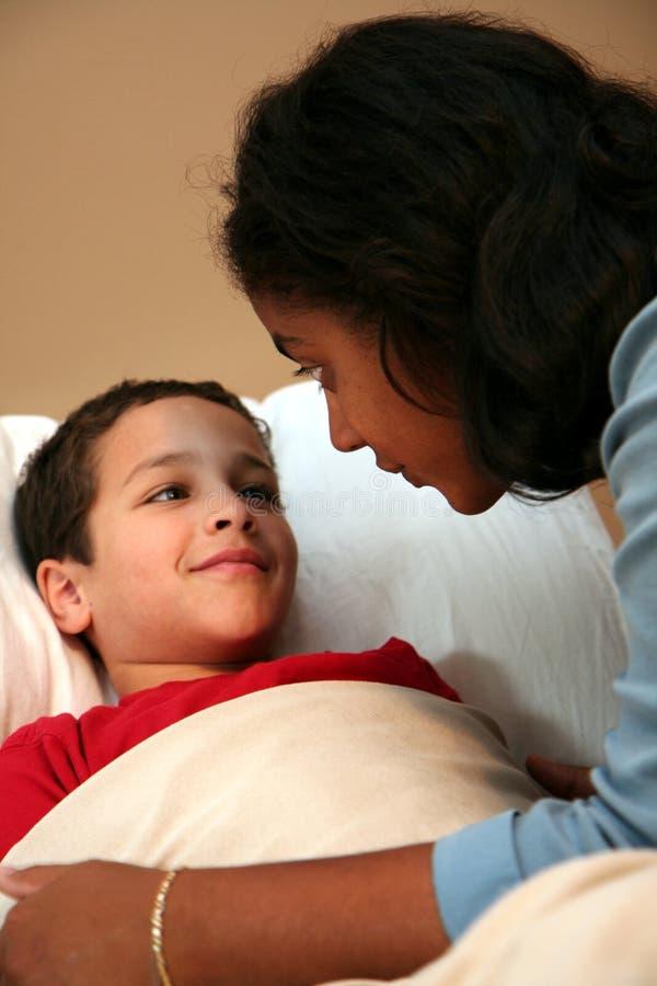 tucking мамы ребенка кровати стоковые фото