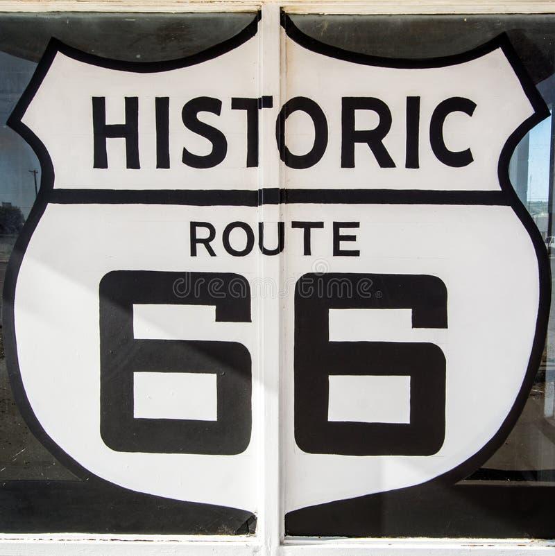 Tucumcari NM/Verenigde Staten - Juli 18, 2016: het reuzeroute 66 -Wegsymbool schilderde teken op een overledene en verlaten sh be stock foto