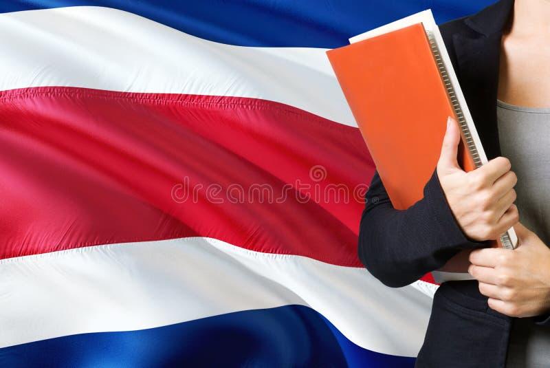 ?tude du concept de langue Position de jeune femme avec le drapeau de Costa Rica à l'arrière-plan Professeur tenant des livres, b photos stock