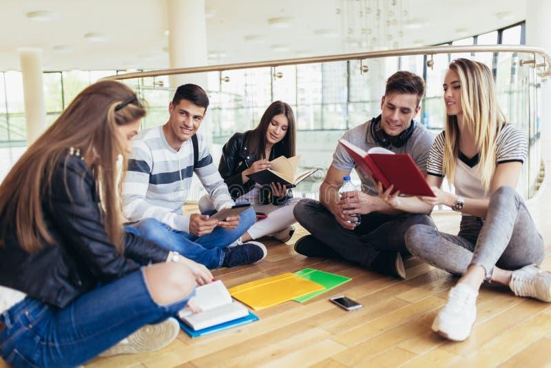 ?tudiants s'asseyant sur le plancher dans le campus et se pr?parant ensemble aux examens photo stock