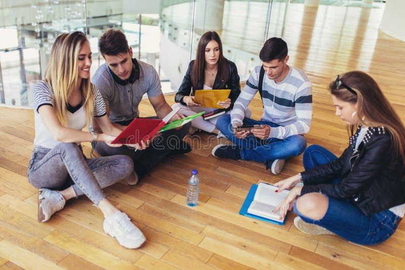 ?tudiants s'asseyant sur le plancher dans le campus et se pr?parant ensemble aux examens image stock