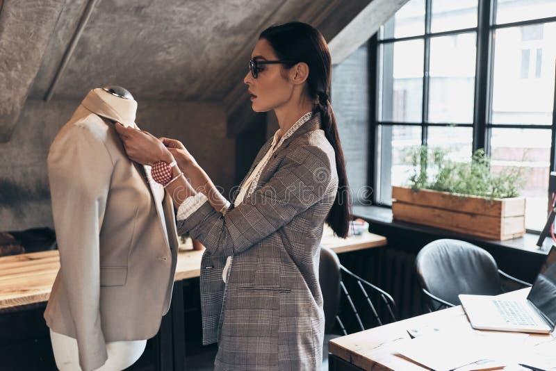 Tudo deve ser perfeito Jovem mulher séria no adjus do eyewear imagem de stock royalty free