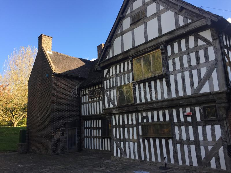 Tudor era building with white walls and beams. And later addition of a brick building which houses a kitchen facility royalty free stock images