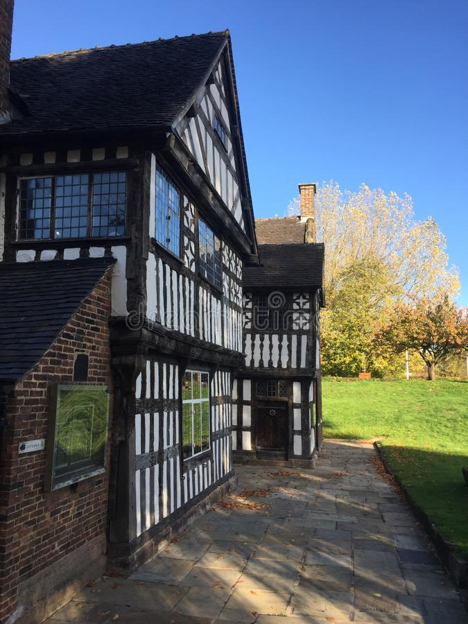 Tudor era building with white walls and beams. Bathed in sun rays and surrounded by lovely green grass and trees, taken in autumn 2018 stock image