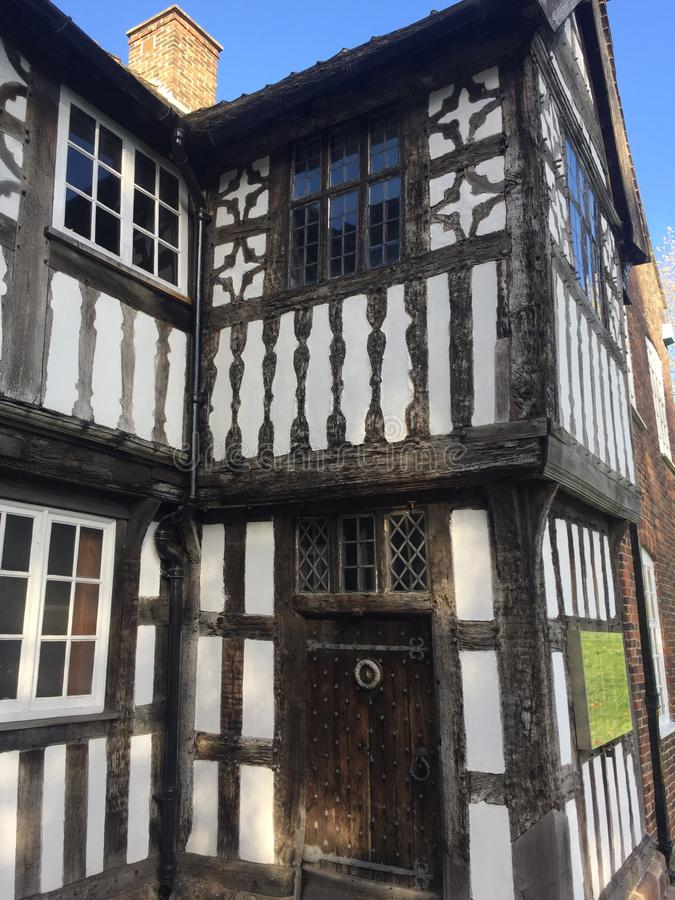 Tudor era building with white walls and beams. This is detail of windows, and main entrance with lovey decoration stock photos