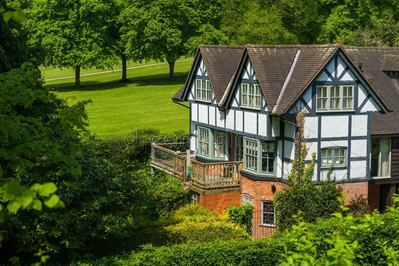 Tudor hus som omges av träd och buskar arkivbilder