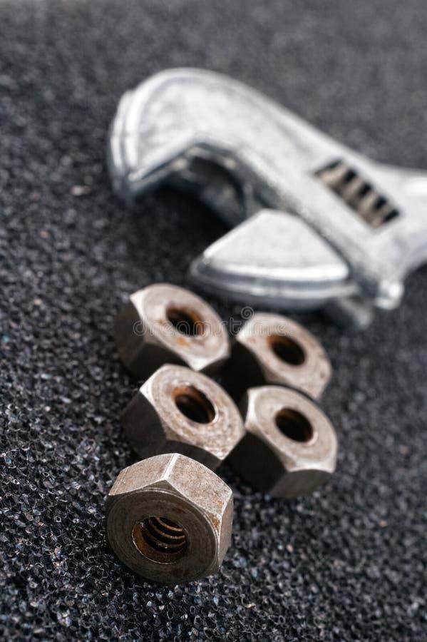 Tuercas y llave inglesa imagen de archivo