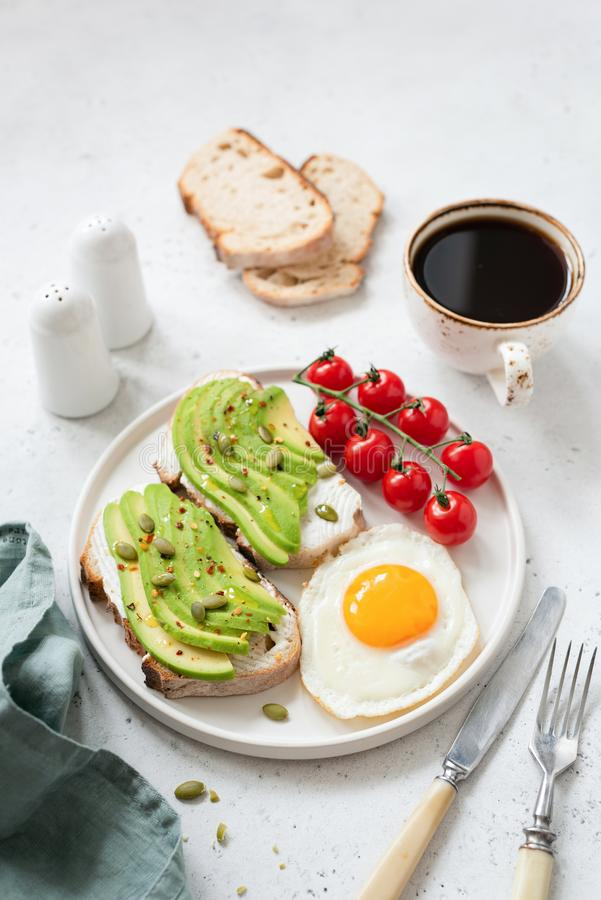 Tueste con el aguacate, el huevo frito, los tomates y el café Comida de desayuno sana fotos de archivo libres de regalías