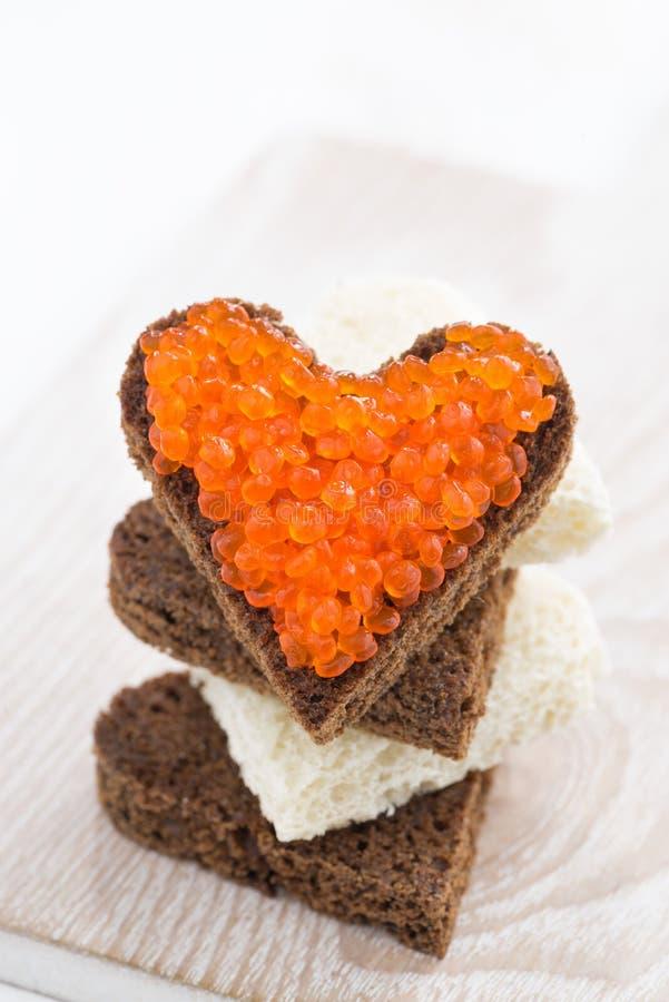 Tueste con el caviar rojo en forma del corazón, primer, vertical imágenes de archivo libres de regalías