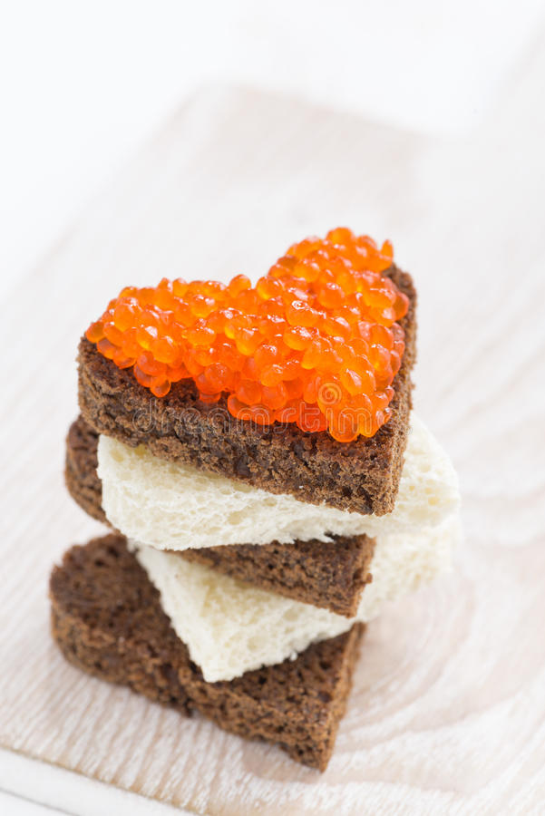 Tueste con el caviar rojo en la forma del corazón, vertical fotografía de archivo libre de regalías