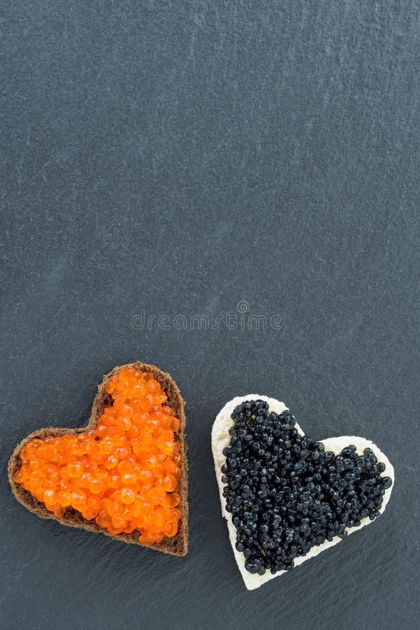 Tueste con el caviar rojo y negro bajo la forma de corazón imagen de archivo libre de regalías
