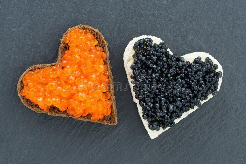Tueste con el caviar rojo y negro bajo la forma de corazón en oscuridad imagen de archivo