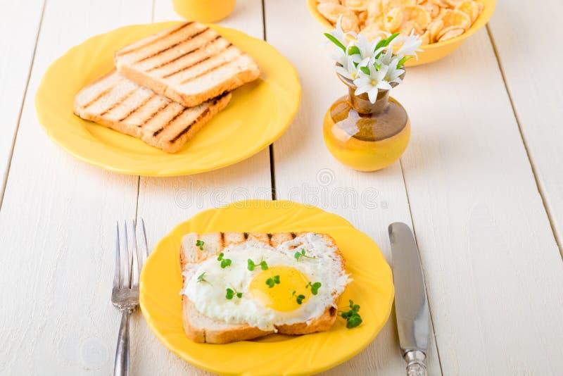 Tueste con el huevo en placa amarilla cerca del florero con la flor en el fondo de madera blanco Desayuno sano imagen de archivo