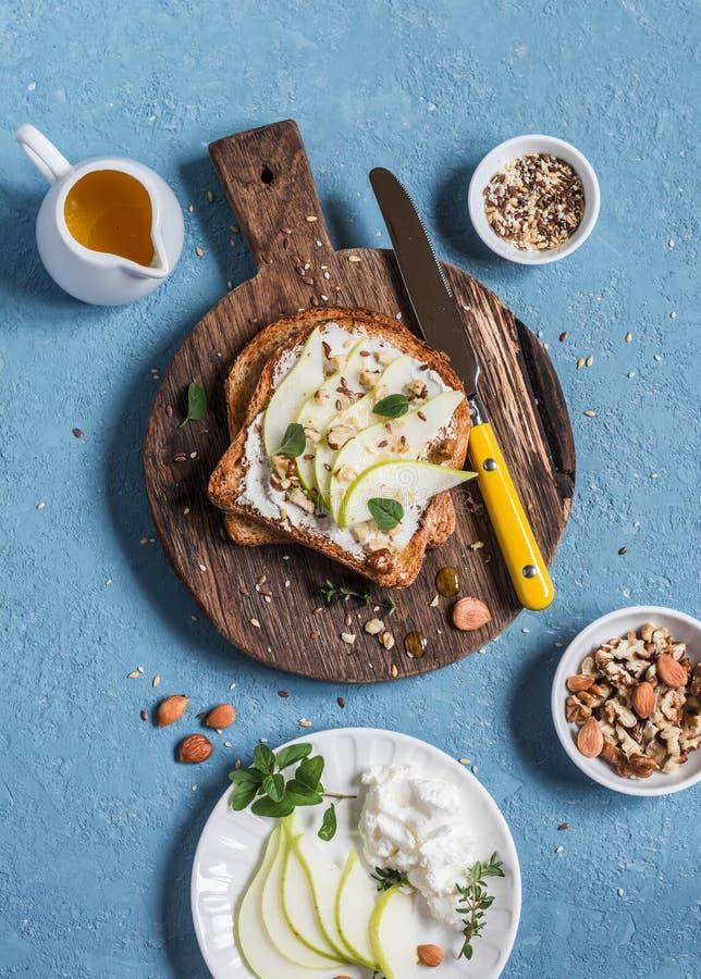 Tueste con queso, la pera, la miel y las nueces Desayuno o bocado delicioso en un fondo azul imagen de archivo