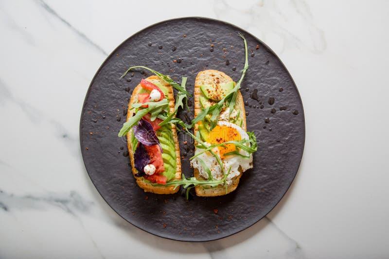 Tueste con veggies, el aguacate, el aragula, la albahaca, el tomate, el queso de la mozzarella y el lado soleado encima del huevo foto de archivo